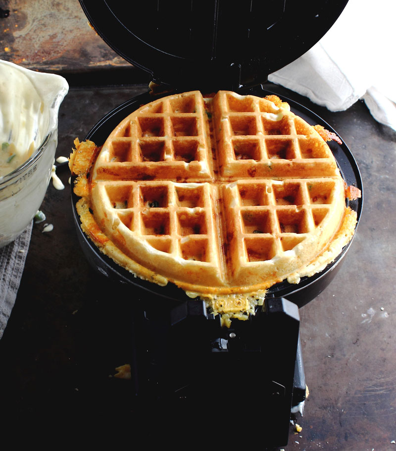 Fully cooked waffle in waffle iron for National Waffle Day Southwestern Waffle Poutine
