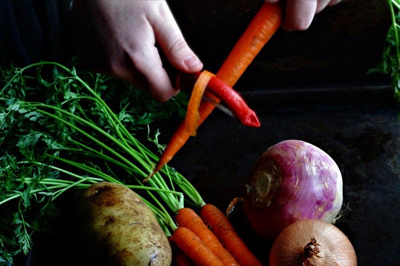 Peeling carrots, potatoes, and turnips for traditional Irish Stew